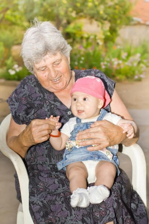 Portrait of smiling senior woman with little granddaughter in the backyard Stock Photo - 15693020
