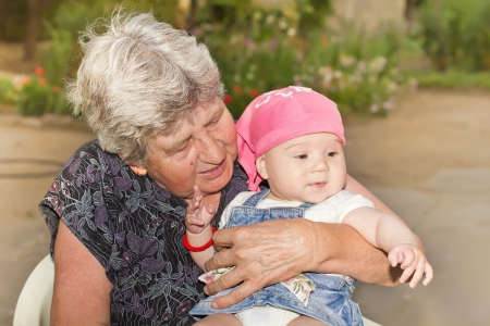 Portrait of smiling senior woman with little granddaughter in the backyard Stock Photo - 15693023