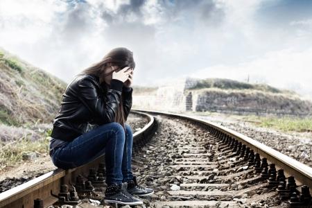 persona confundida: Lonely girl adolescente con las manos en la cara que se sienta en el ferrocarril