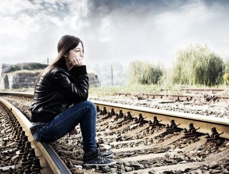 adolescencia: Adolescente solitario que se sienta en ferrocarril y de pensar.