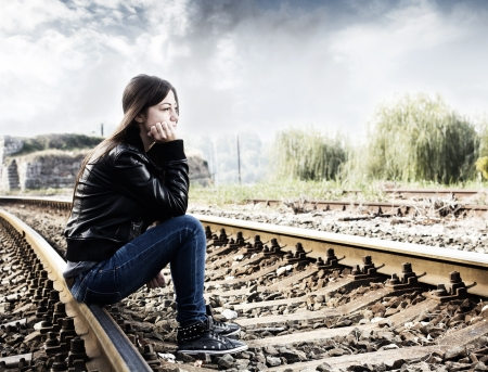 Lonely teenage girl sitting on railroad and thinking. Stock Photo