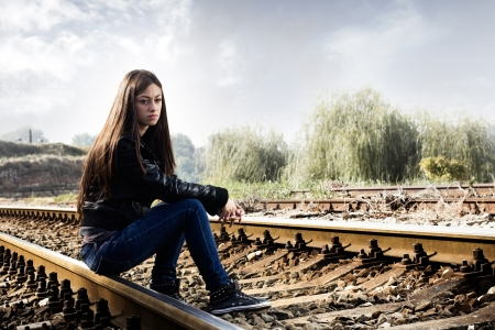 sad lonely girl: Lonely teenage girl sitting on railroad and thinking. Stock Photo