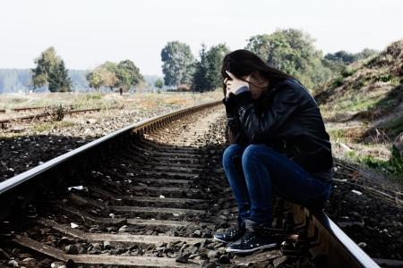 depressione: Lonely girl adolescente con le mani sul suo viso si siede sulla ferrovia Archivio Fotografico