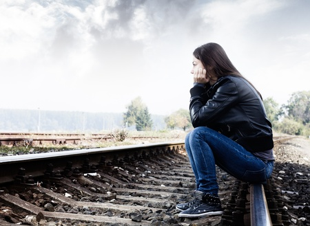 Sad teenager sitting on the tracks, looking into the distance and thinking. Stock Photo