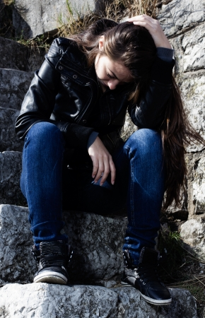 Sad teenager sitting on old stone stairs and thinking. Foto de archivo