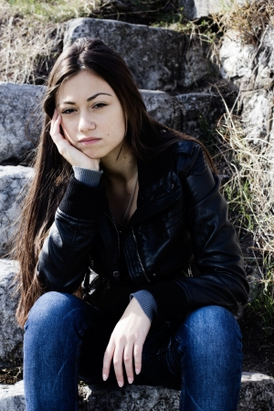 Sad teenager sitting on old stone stairs and thinking. Stock Photo