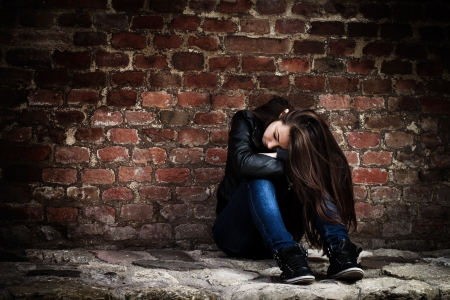 Sad teenage girl, leaning on an old brick wall.
