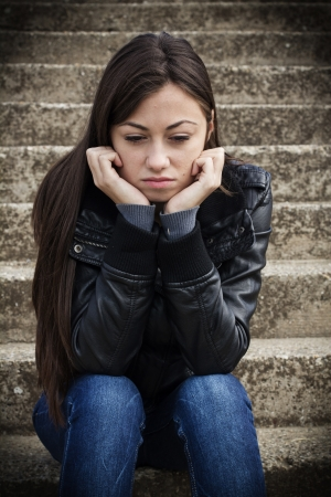 confused woman: Portrait of depressed teenage girl sitting on staircase.