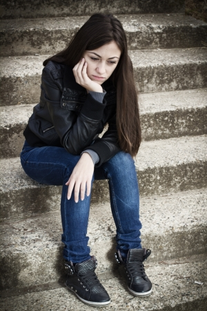 Portrait of depressed teenage girl sitting on staircase. photo
