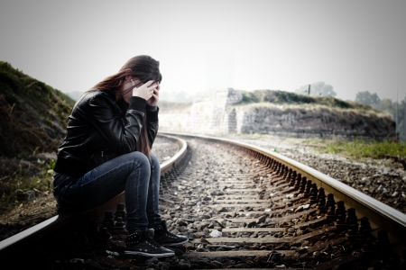hopelessness: Depressed and lonely teenage girl with hands over her face sitting on the railroad Stock Photo