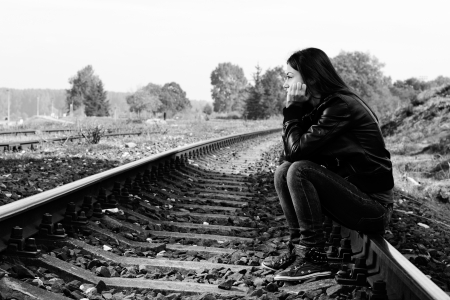Depressed and lonely teenage girl with hands over her face sitting on the railroad Standard-Bild
