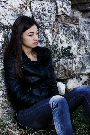 Depressed and lonely teenage girl, sad expression face, leaning on stone wall. photo