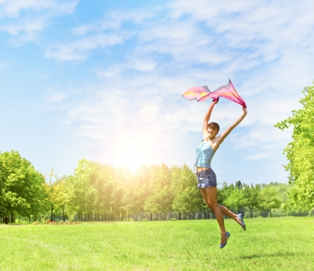 Happiness girl jumping on the green fields at beautiful summer day. photo