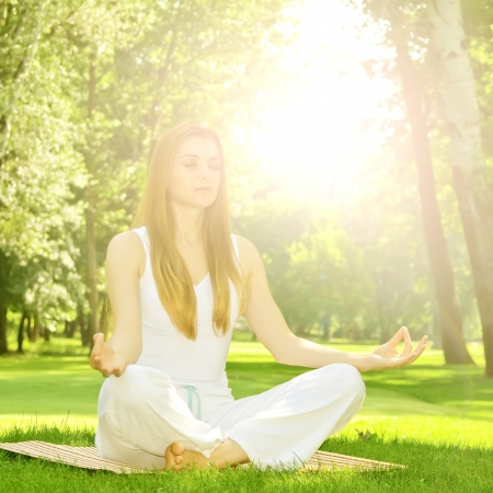 Young woman practicing yoga meditation in the park. photo