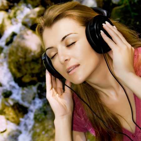 Beautiful girl listen music by headphones in natural environment. photo
