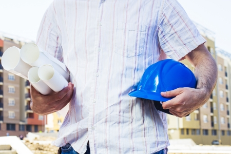 Closeup of construction worker holding project and blue hard hat, photo