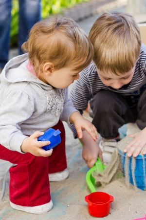Kids playing in playground with sand and toys. photo