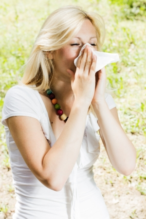 allergic reaction: Young woman blowing nose outdoor, pollen allergy,
