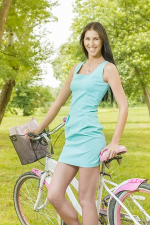 Attractive girl with bicycle in the park at beautiful spring day. photo