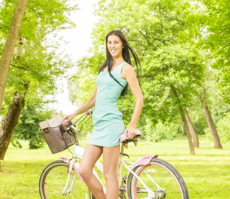 Happy attractive girl with bicycle in the park at beautiful spring day. photo