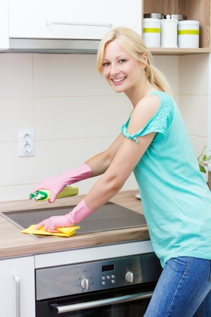 Beautiful housewife cleaning in the kitchen. photo