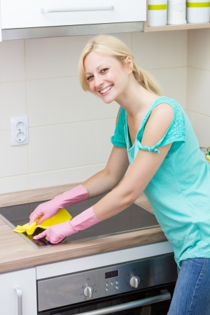 housewife gloves: Beautiful housewife cleaning in the kitchen.
