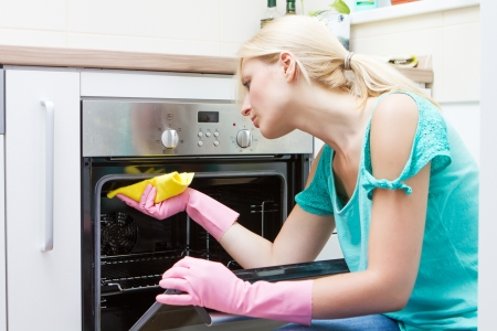 oven: Young woman cleaning oven in the kitchen.