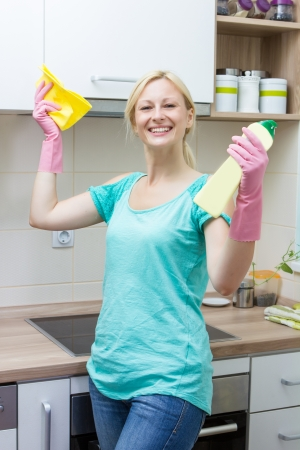 housewife gloves: Happy housewife cleaning in the kitchen.