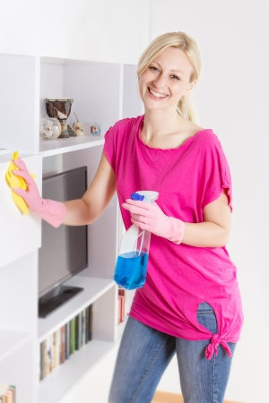 Happy housewife cleaning furniture at home.