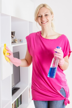 housemaid: Happy housewife cleaning furniture at home.