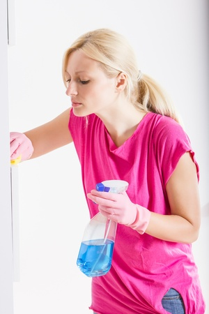housemaid: Young woman cleaning furniture at home.