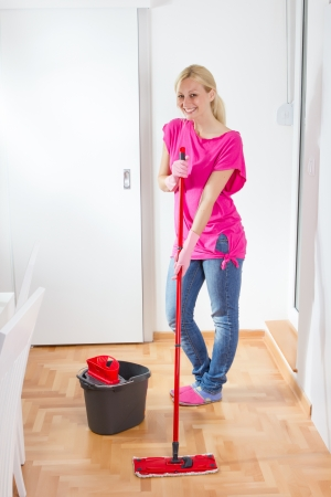 mopping: Young woman cleaning and mopping floor at home.