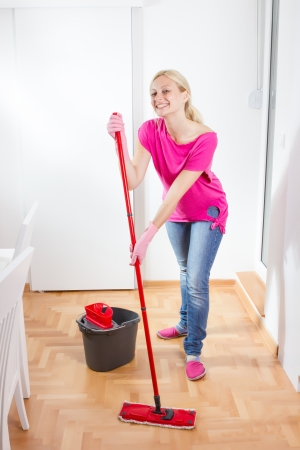Happy woman cleaning and mopping floor at home. photo