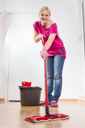 Young woman cleaning and mopping floor at home. photo