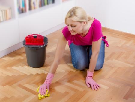твердая древесина: Молодая женщина, очистки и уборки этаже дома.