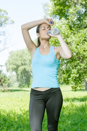 Fitness girl refreshment drinking water in the park. photo