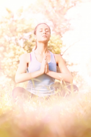 Young woman meditating in the park. photo