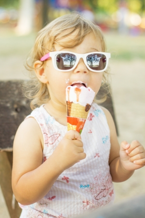 Cute baby girl eating ice cream outdoor. photo