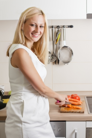 Portrait of happy blonde woman preparing vegetable in the kitchen. photo