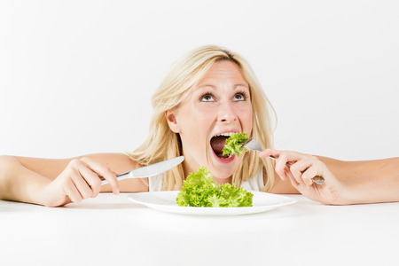 Portrait of happy woman eating green salad for meal. photo