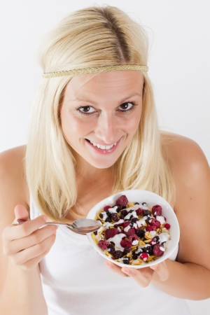 Portrait of lovely blonde woman eating cereals with fruit at breakfast. photo