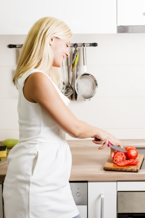Portrait of young blonde woman preparing vegetable in the kitchen. photo