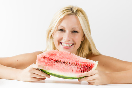 Happy young woman eating fresh watermelon. photo