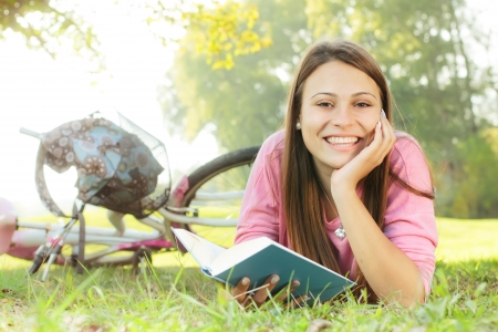 Happy student girl relaxing on green grass reading book.Bicycle in the background. photo