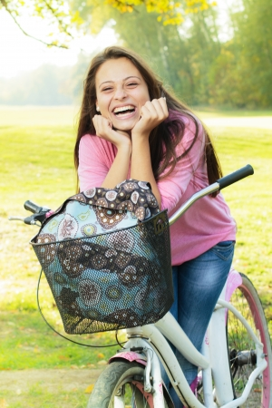 Portrait of smiling student girl with bicycle in the park. photo