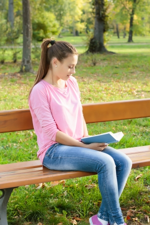 Student girl reading book on the park bench. photo