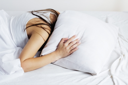 hangover: Girl covered her head with a pillow.Insomnia  Stock Photo