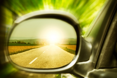 Sunset on a lonely country road, as seen in car mirror