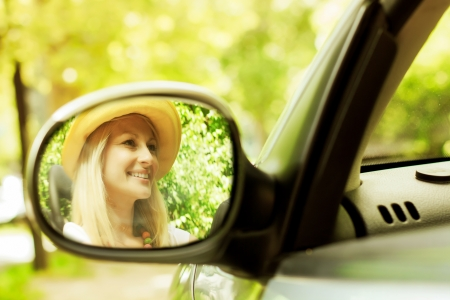 Cheerful beautiful young woman in the car, reflection in the mirror  photo