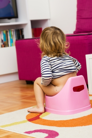 potty training: Little girl sitting on the potty at home.
